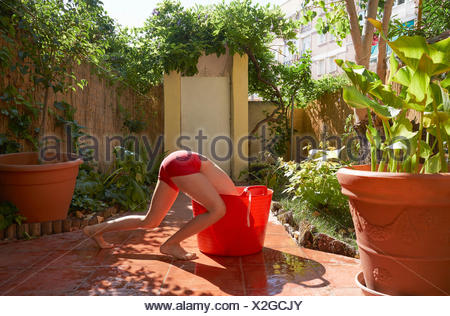 Girl in bikini bottoms bending headfirst into red bucket on patio - Stock Photo