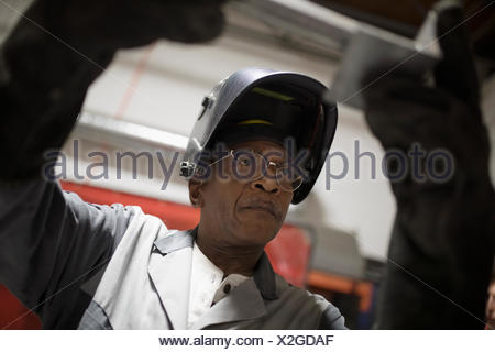 Senior male welder examining metal piece - Stock Photo