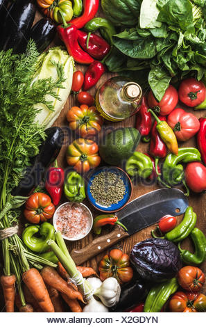 Variety of fresh raw vegetables for healthy cooking or salad making and carving knife, top view. Diet or vegetarian food concept - Stock Photo