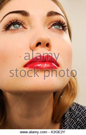 A young woman wearing red lipstick looking up - Stock Photo
