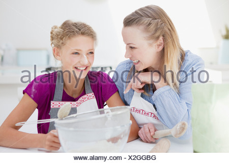 Mother and daughter with flour on nose baking in kitchen - Stock Photo