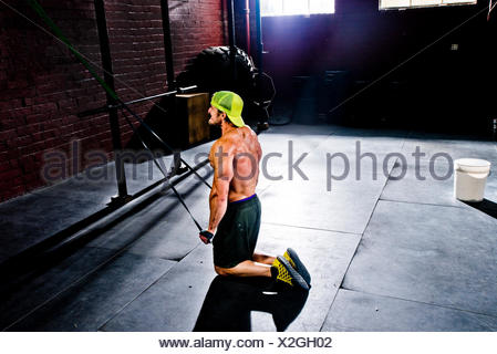 A crossfit athlete working out with resistance bands. - Stock Photo