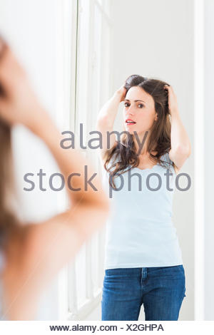 Woman checking her face in the mirror. - Stock Photo
