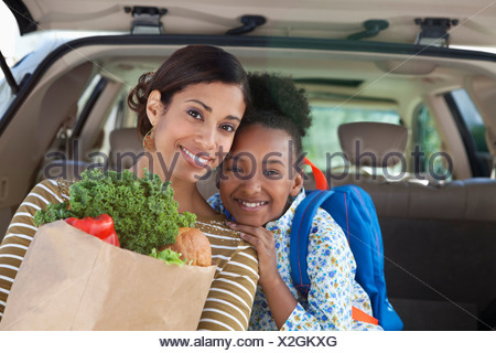 Mother and daughter unloading groceries from car - Stock Photo