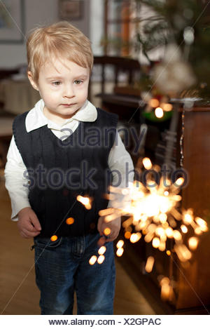 little boy standing in the living room watching a burning sparkler in hand - Stock Photo