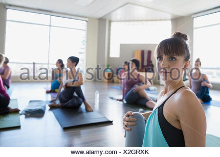 Women practicing seated twist pose in yoga class - Stock Photo