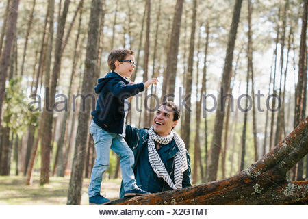 Happy father assisting son in climbing tree at forest - Stock Photo