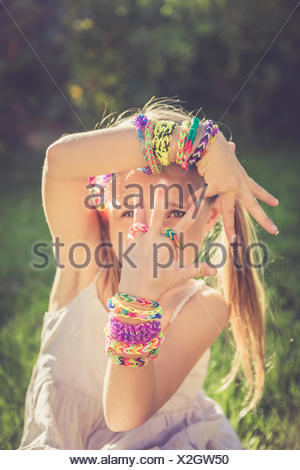 Portrait of little girl showing her loom bracelets and rings - Stock Photo
