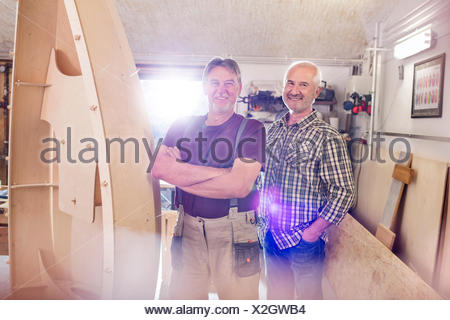 Portrait smiling male carpenters making wood boat in workshop - Stock Photo