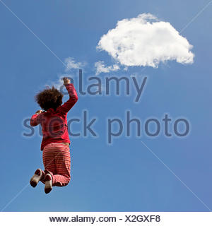 Rear view of girl jumping in the air - Stock Photo