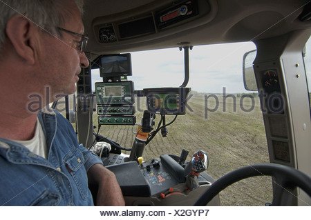 Case 225 tractor interior and farmer with GPS and Samson vacuum slurry tanker control panel injecting slurry into stubble field - Stock Photo