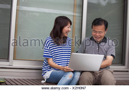 A man and a women sitting outside a house. Holding a laptop computer. - Stock Photo