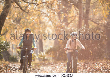 Mother and daughter bike riding on path in woods - Stock Photo