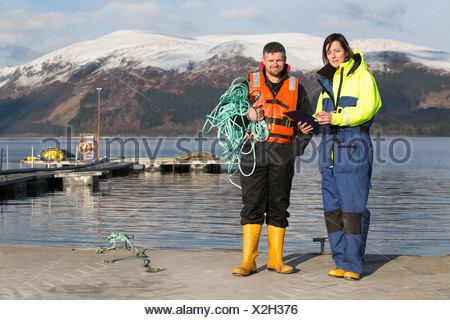 Workers on salmon farm in rural lake - Stock Photo