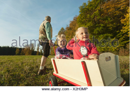 Germany, Bavaria, Grandfather pulling granddaughters sitting in wagon - Stock Photo