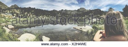 Rear View Of Woman Sitting On Lakeshore Against Cloudy Sky - Stock Photo