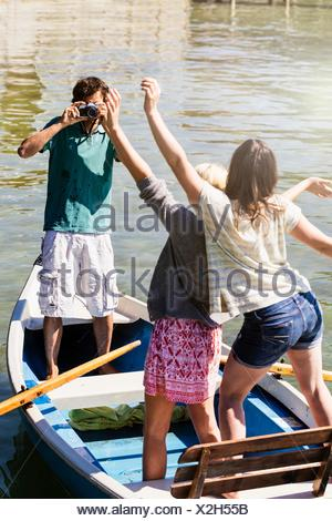 Young man in boat on lake photographing women - Stock Photo
