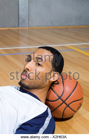 A young man rests his head on a basketball - Stock Photo