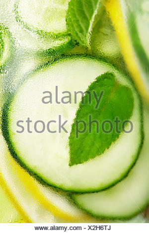 Infused water with cucumber, lemon, lime and mint on blue background - Stock Photo
