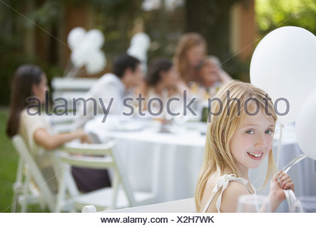Young girl sitting at outdoor party with balloons smiling - Stock Photo