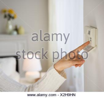 Woman adjusting digital thermostat - Stock Photo