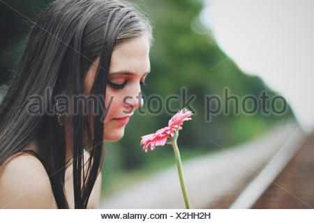 Young woman smelling gerbera flower - Stock Photo