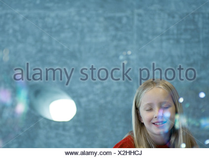 Girl closing eyes as bubbles float in the air - Stock Photo