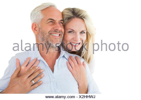 Smiling couple embracing with woman looking at camera - Stock Photo