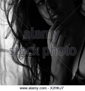 Portrait Of Woman With Hands On Chin At Home - Stock Photo