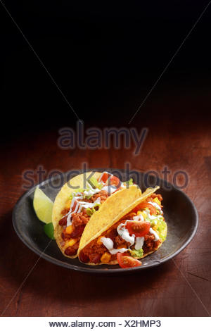 Mexican corn taco filled with spicy ground meat , salsa and salad served in a shallow wooden bowl on a wooden table with copyspace - Stock Photo