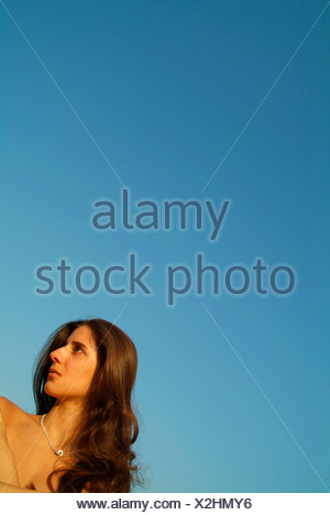 Portrait of woman in front of blue sky - Stock Photo