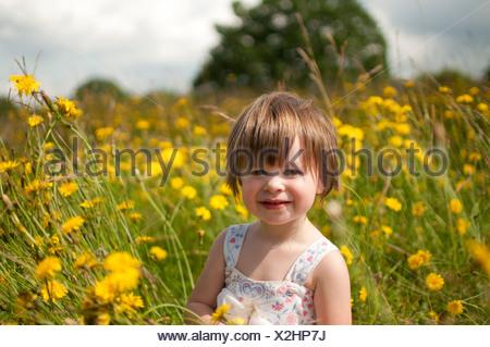 A portrait of a little girl in a wild flower meadow - Stock Photo