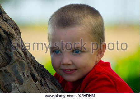 Autistic boy trying to climb a palm tree at the beach. - Stock Photo