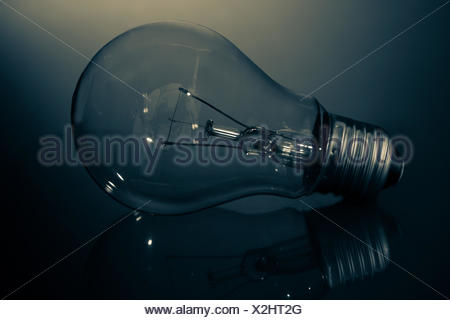 Clear light bulb lay on its side in darkness on reflective surface - Stock Photo