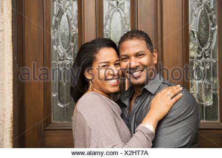 Portrait of happy mid adult couple at front door - Stock Photo