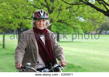 Senior woman riding bicycle in park, portrait - Stock Photo