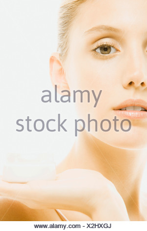 Young woman holding jar of moisturizer, cropped - Stock Photo