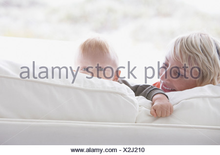 Woman with baby peering over sofa - Stock Photo