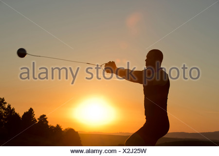 Young man preparing to throw the hammer at sunset - Stock Photo