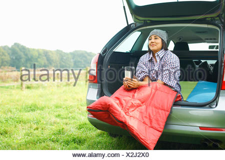 Woman sitting at rear of car with legs tucked in sleeping bag - Stock Photo