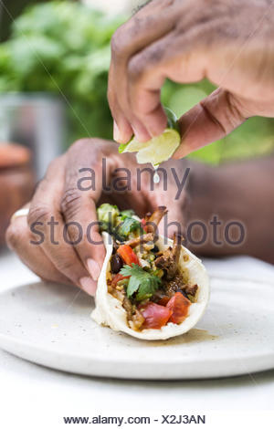 A man is squeezing lime on a slow cooked beef brisket chili taco while holding it with his other hand. - Stock Photo