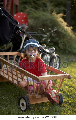 Little girl sitting in a wooden barrow with pacifier in her mouth - Stock Photo