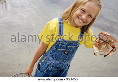 Ten years old girl on beach proudly showing the crab caught while crabbing on vacation. - Stock Photo
