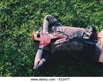 High Angle View Of Young Man Resting On Grass - Stock Photo