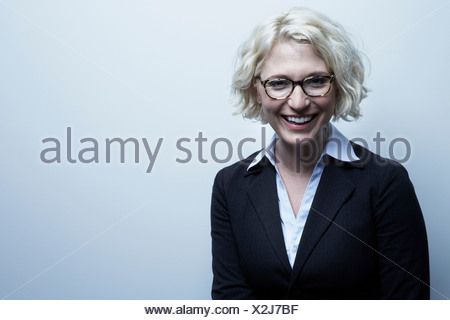 Studio portrait of blond businesswoman smiling - Stock Photo