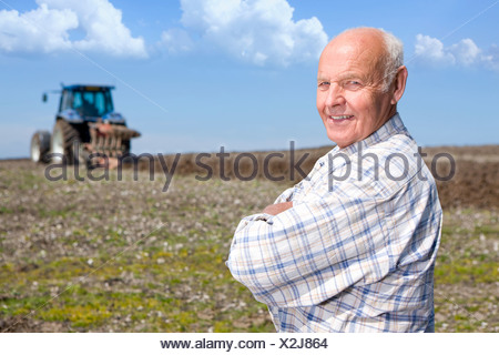 Farmer standing in field with tractor and plough in background - Stock Photo