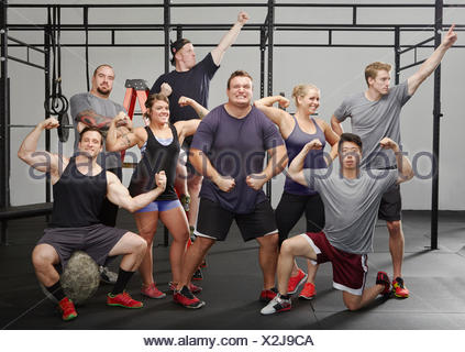 Portrait of eight people flexing muscles in gym - Stock Photo