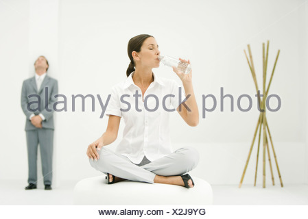Professional woman sitting on ottoman, drinking from water bottle, businessman and bamboo in background - Stock Photo