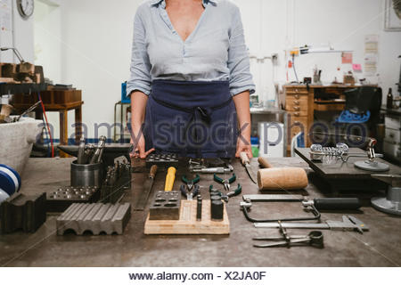 Mid section of female jeweller laying out hand tools at workbench in jewellery workshop - Stock Photo