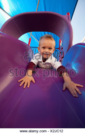 Fort Lauderdale, Florida, United States Of America; A Young Boy Playing On A Slide At The Playground - Stock Photo